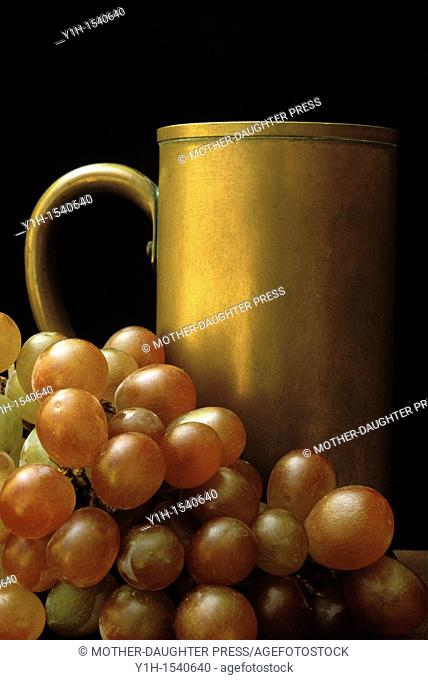 Antique copper mug beside rich red copper grapes