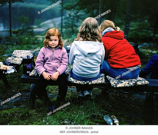 Three people sitting on a bench, Angermanland, Sweden