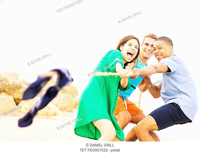 Young people pulling rope on beach