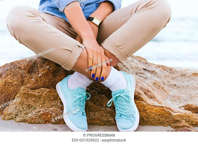 Woman in beige pants and a denim shirt and turquoise sneakers sitting on a rock by the sea. Shirt sleeves rolled up, watch on his arm, a blue manicure