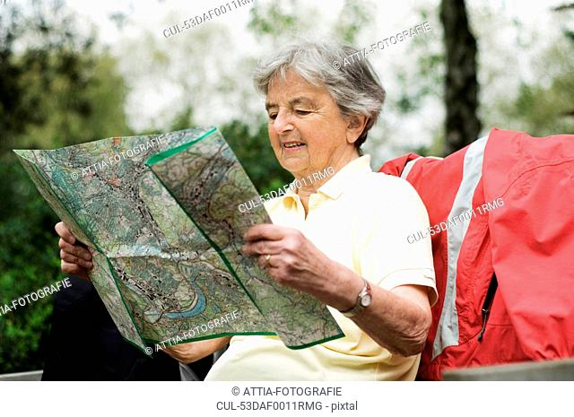 Older woman reading map in park