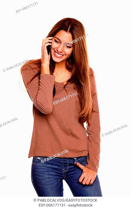 Portrait of a charming young woman with long brown hair speaking on cellphone against white background
