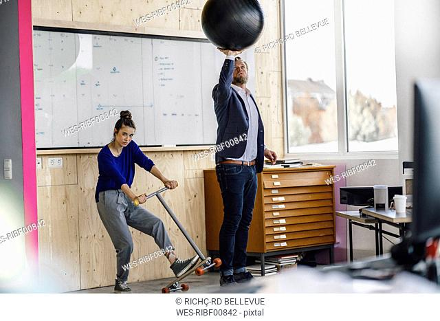 Mature man and his assistent playing with scooter, standing in office in front of white board