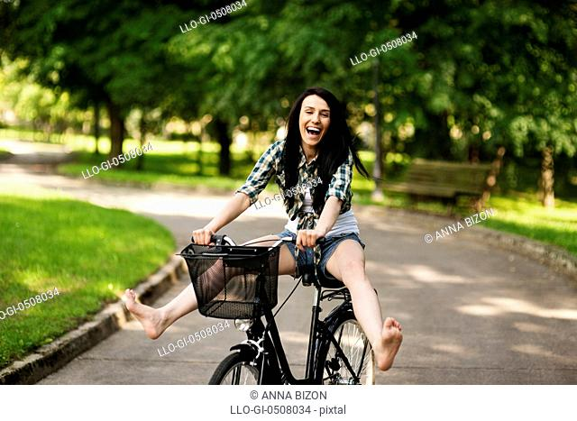 Happy young woman cycling through the park, Debica, Poland