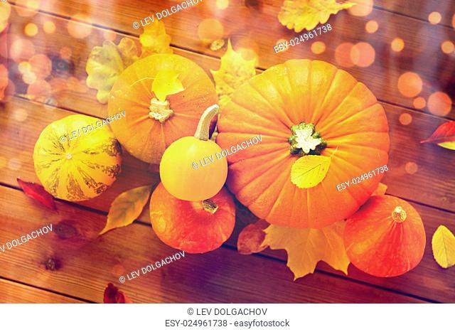 harvest, season, advertisement and autumn concept - close up of pumpkins and leaves on wooden table at home