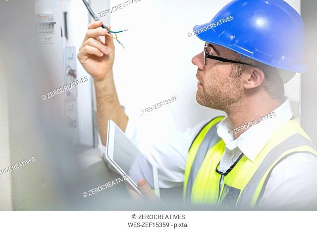 Electrician inspecting wire at fusebox