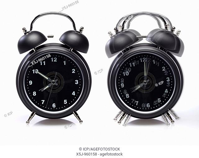 Two alarm clocks one still ringing - on white background