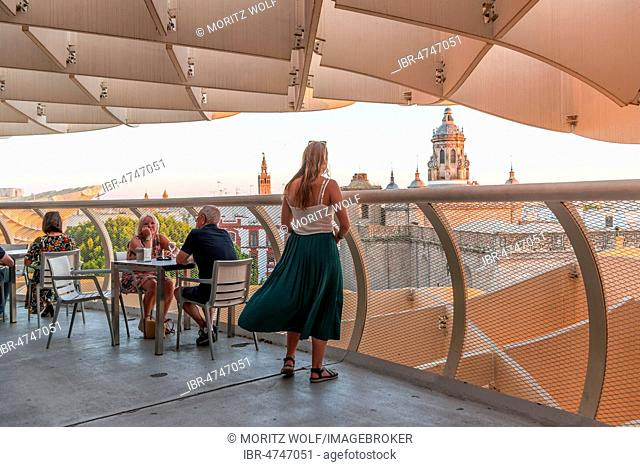 Woman looks at cathedral, restaurant and bar on the Metropol Parasol, curved wooden structure, Plaza de la Encarnacion, Seville, Andalusia, Spain
