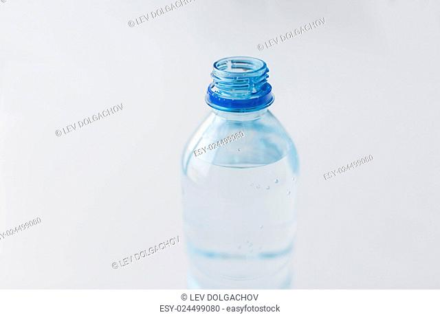 recycling, healthy eating and food storage concept - close up of open plastic bottle with pure drinking water on table