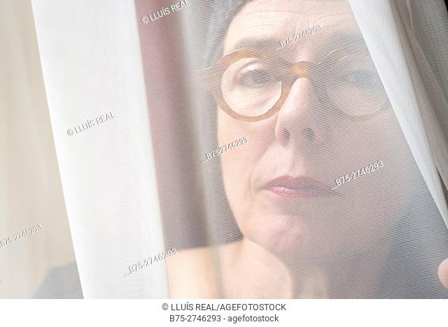 Close-up portrait of mature woman with eyeglasses looking at camera behind curtain