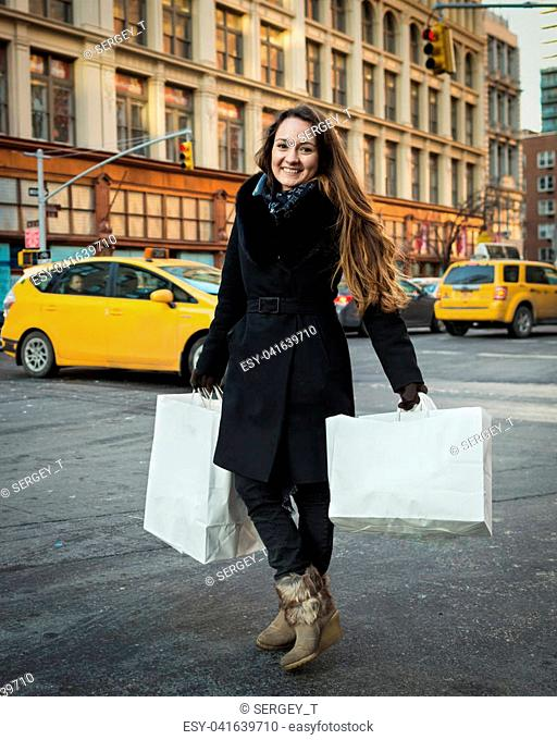 Young woman with shopping bags standing and smiling at a busy intersection. One Person. NYC