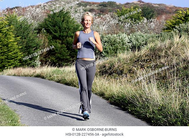Blonde woman outdoors. Jogging along country road