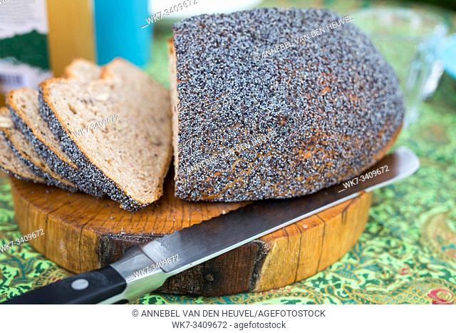 Fresh homemade bread on cutting board with knife on colorful breakfast table close-up