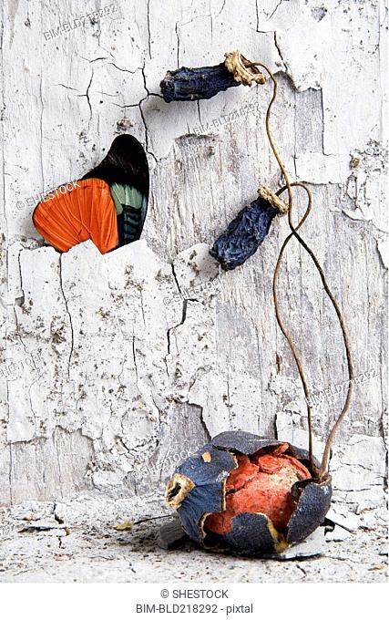 Egg in cracked shell under dilapidated wall and butterfly