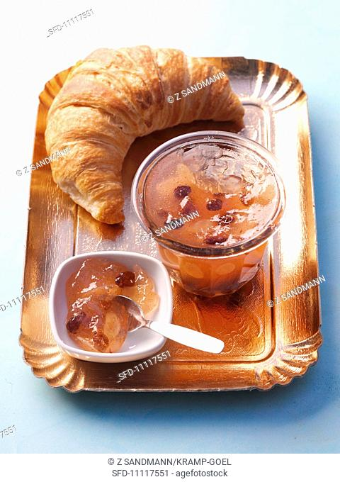 A croissant with apple jelly with almonds