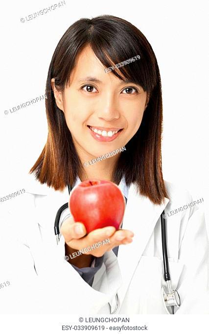 Asian female doctor holding red apple