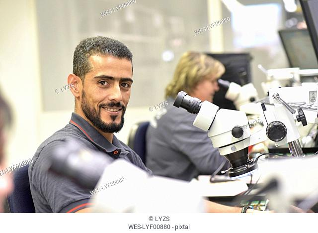Portrait of smiling man working on quality control in the manufacturing of circuit boards for the electronics industry