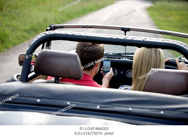 A young couple driving in the countryside, man looking navigating using a smartphone