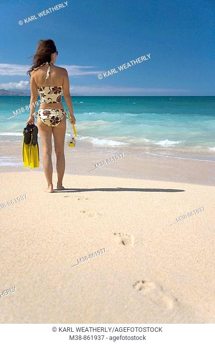 Woman holding snorkel gear on the beach  Maui, Hawaii