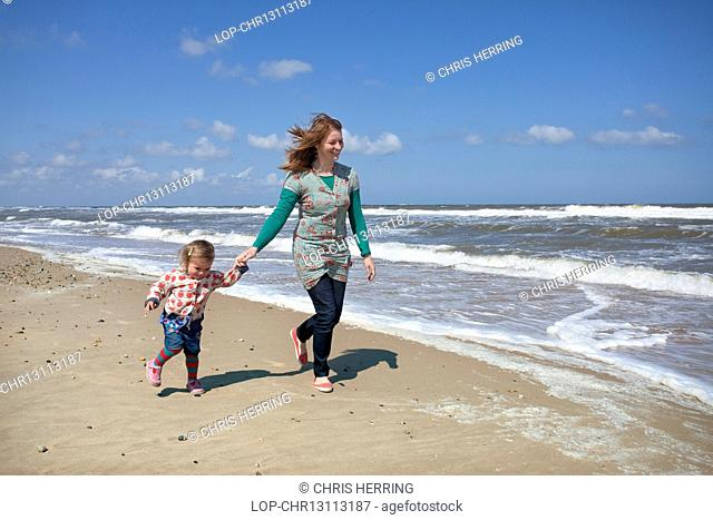 England, Norfolk, Horsey. A mother and daughter running along the beach at Horsey on the Norfolk coast