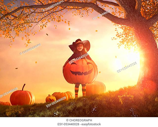 Happy Halloween! Cute little witch with a big pumpkin. Beautiful young child girl in costume outdoors
