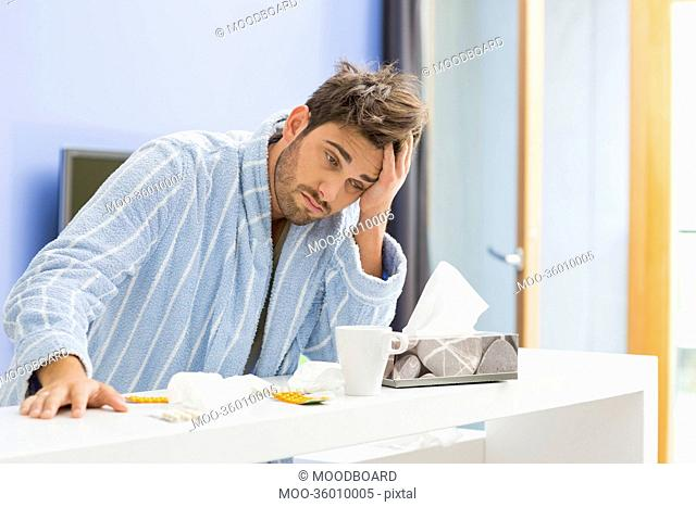 Young ill man with coffee mug, medicine and tissue leaning on kitchen counter