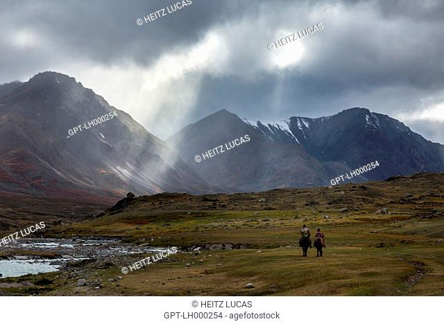 KAZAKH RIDERS BENEATH THE RAYS OF LIGHT IN CLOUDY WEATHER, REDDISH HILLS WITH SNOW-COVERED SUMMITS IN THE DISTANCE, TAVAN BOGD MASSIF, ALTAI