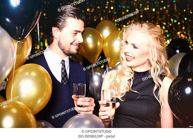 Young man and woman at party, holding champagne glasses, smiling