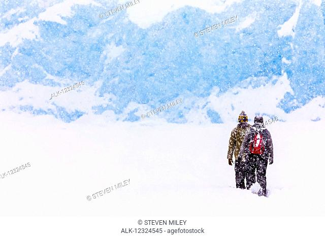 A couple snowshoes across Portage Lake during a heavy snowfall in winter to see the terminus of Portage Glacier, Southcentral Alaska, USA