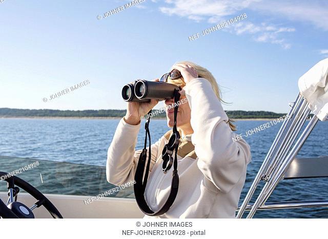 Woman on boat looking through binoculars