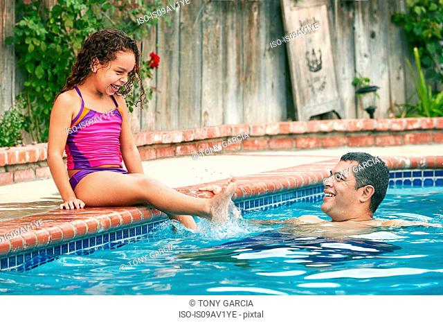 Girl wearing swimwear sitting poolside splashing father smiling