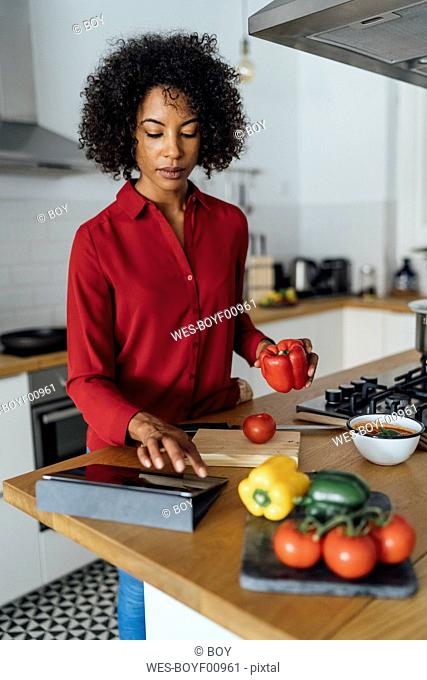 Woman standing in kitchen, chopping vegetables, using digital tablet
