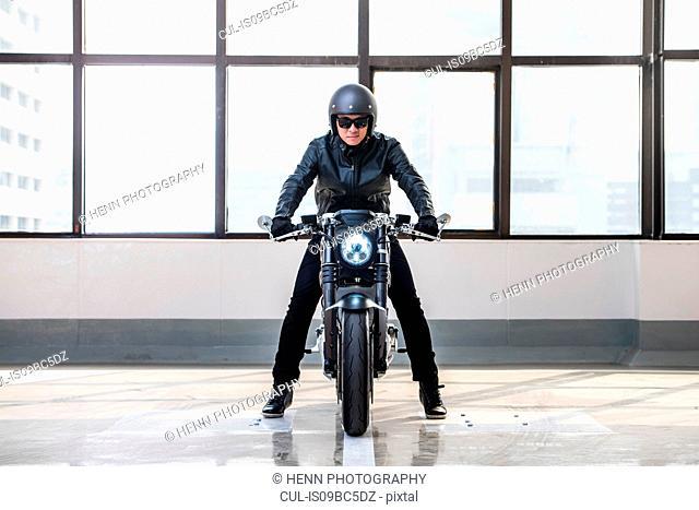 Portrait of man on electric cafe racer motorbike, inside garage