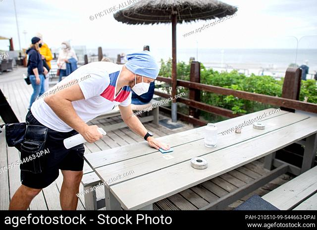 10 May 2021, Lower Saxony, Norderney: Employee Tobias wipes down a table on the terrace of the Surfcafe on the beach promenade