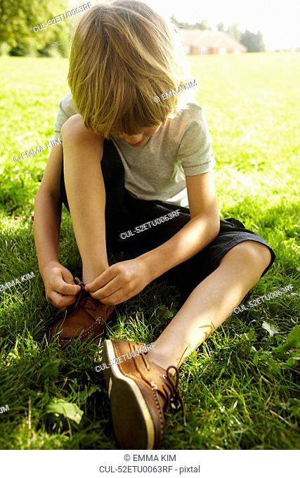 Boy tying his shoe in grass