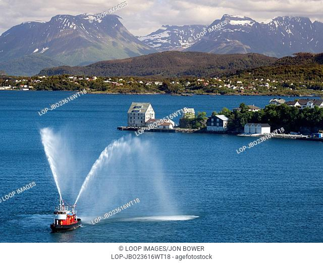 A fireboat saluting a cruise liner leaving the harbour in Alesund in Norway