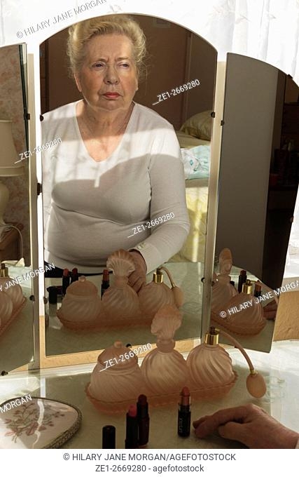 Elderly lady looking at her reflection in an old fashioned dresing table mirror