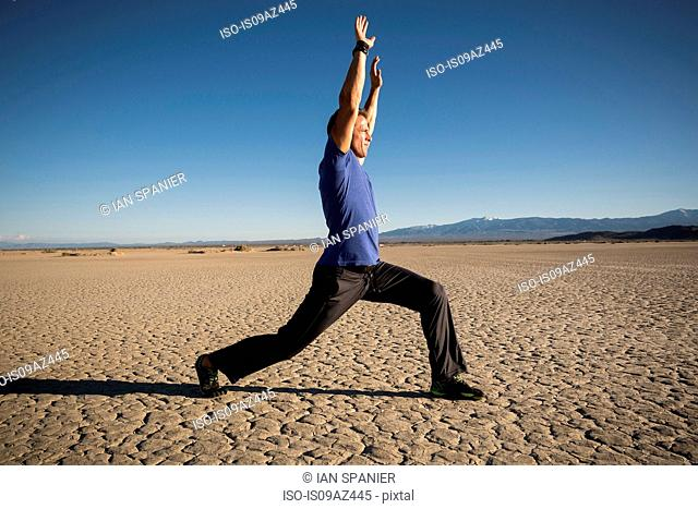 Man training, stretching arms on dry lake bed, El Mirage, California, USA