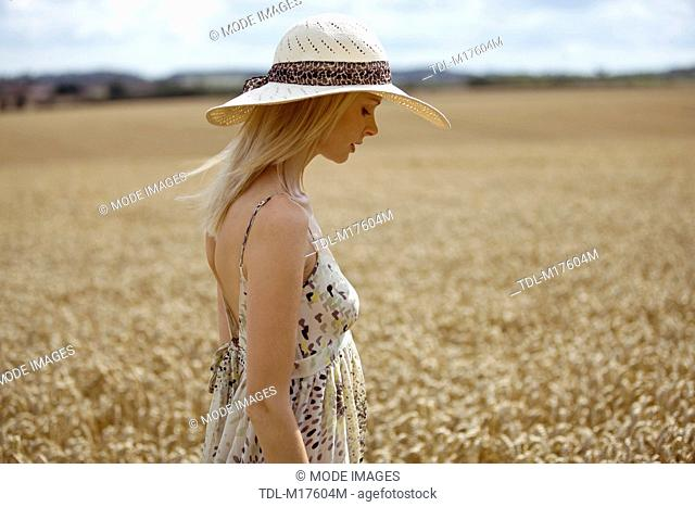 A young woman walking through a wheat field in summertime