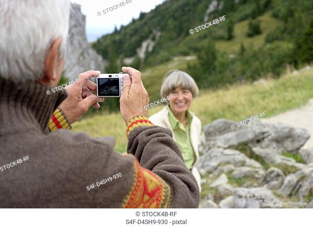 Senior adult man taking a picture of his wife in the mountains, selective focus