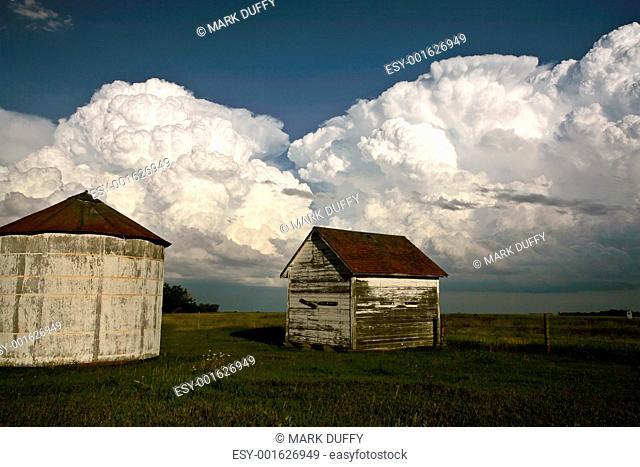 Storm clouds behind old Saskatchewan granaries