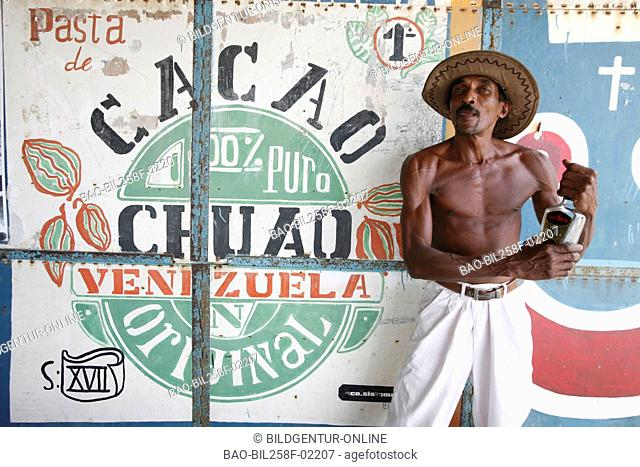 A farmer with a bottle of rum in a cocoa plantation in Chuao in the Caribbean in Venezuela in South America