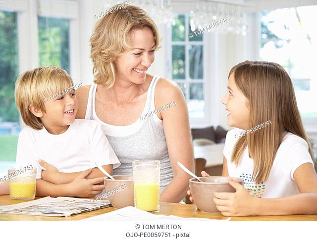Woman and two kids in kitchen eating breakfast
