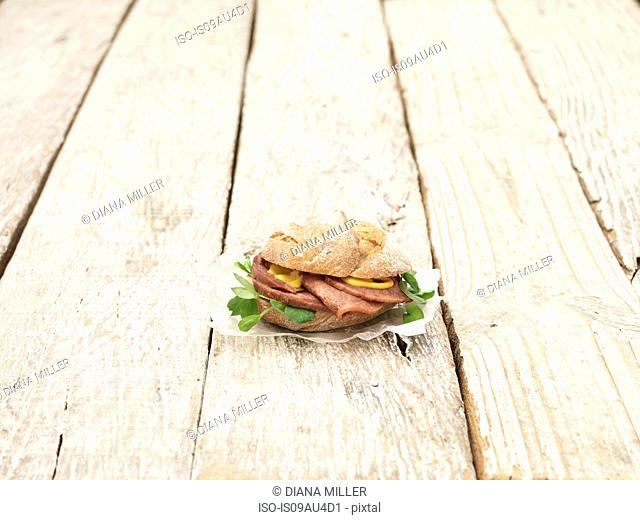 Ox tongue and mustard sandwich in crusty bread bun on whitewashed table