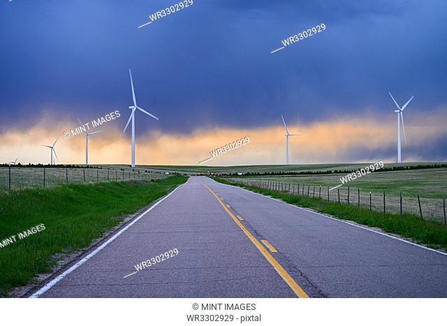 Wind turbines near road at sunset