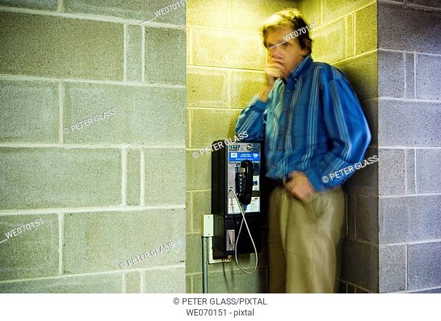Man standing next to a pay telephone