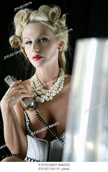 Portrait of sexy blonde woman in lingerie holding phone