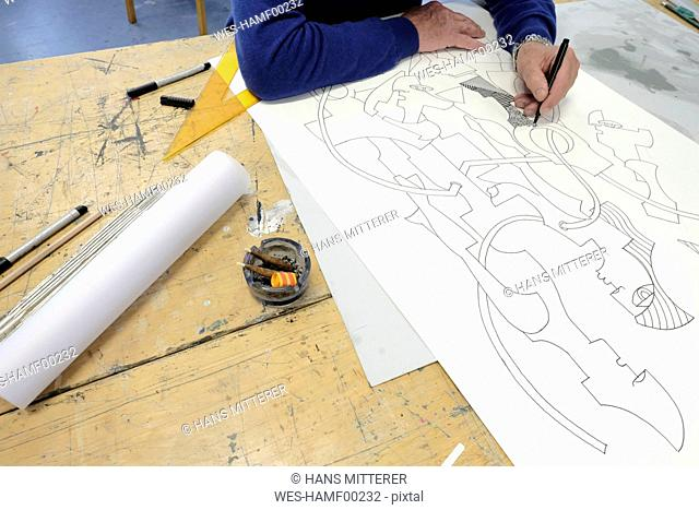 Artist drawing at desk, partial view