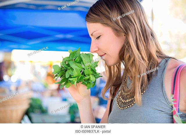 Woman at fruit and vegetable stall smelling fresh herbs