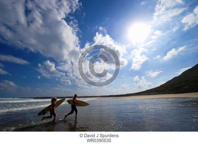 Two surfers running along the beach having fun